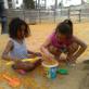 Dues nenes de petits juguen a cuines al sorral del parc